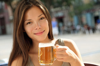 Woman drinking beer on a terrace cafe